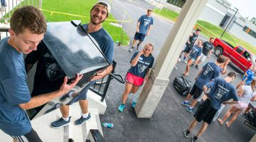 Volunteers help new students move into residence halls