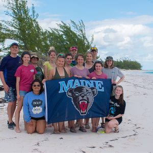 Students on beach with UMaine Banner in Bahamas 2019