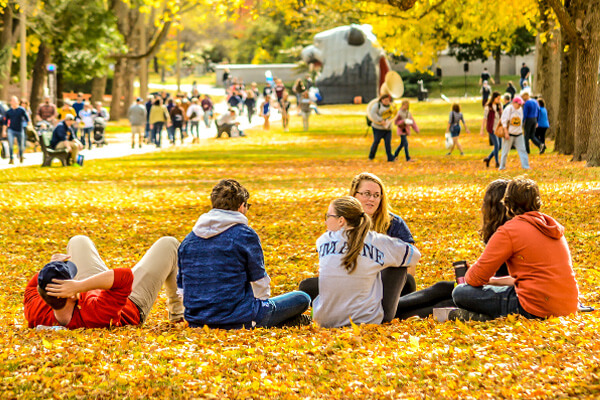 Students sitting on the mall surronded by fall leaves